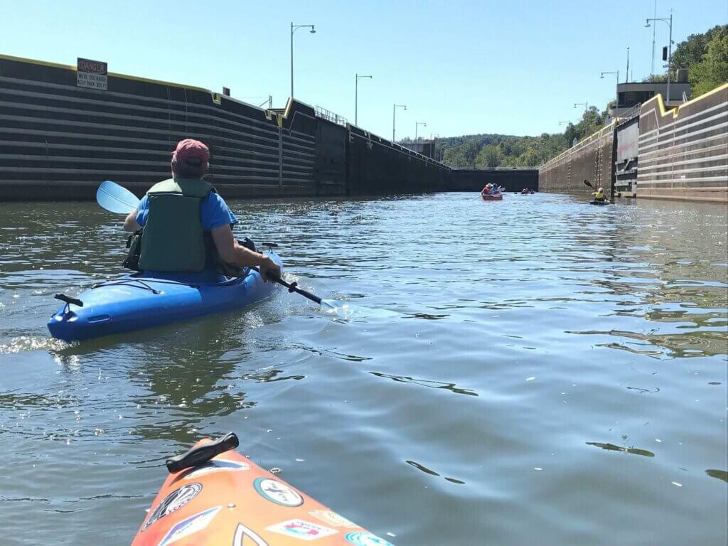Kayakers move through locks on Mon River