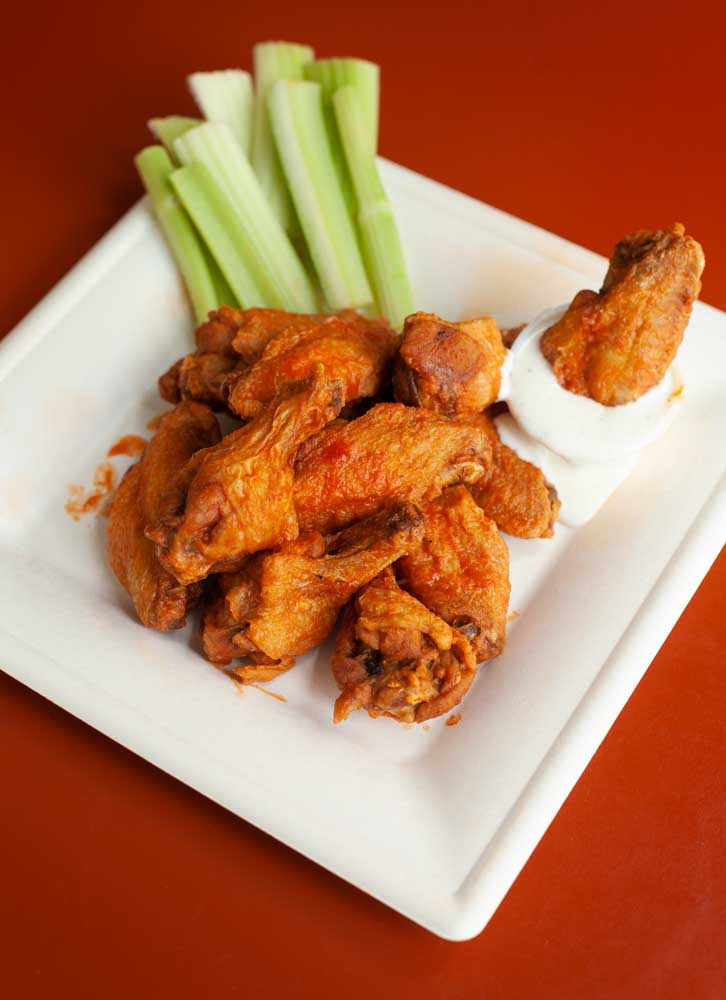 Traditional buffalo wings with celery and ranch dipping sauce on a plate ready to eat.
