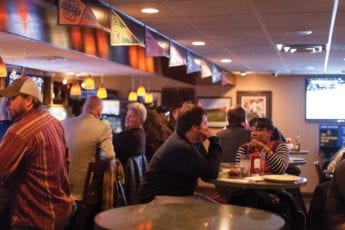 People in sports bar watching football on televisions