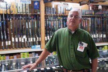 Man in front of gun counter in family owned store